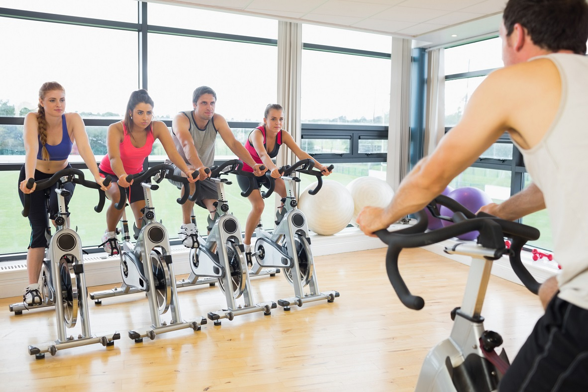 Cropped man teaching spinning class to four people in gym